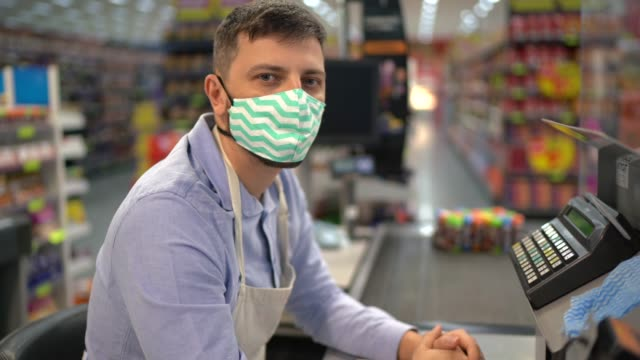 portrait of cashier supermarket employee with face mask - cashier stock videos & royalty-free footage