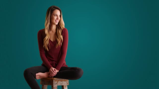 portrait of caucasian woman sitting on stool and laughing on blue background - stool stock videos & royalty-free footage