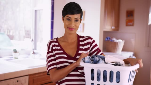vídeos de stock, filmes e b-roll de portrait of cheerful black female holding laundry basket in kitchen, laughing - domestic kitchen