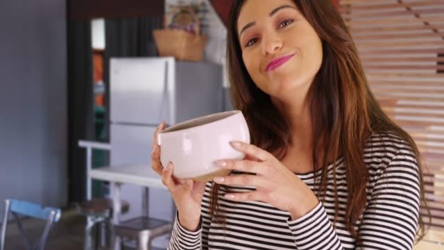 stockvideo's en b-roll-footage met portrait of cheerful latina female holding up ceramic bowl, smiling at camera - natuurlijk haar