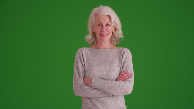 portrait of cheerful mature woman in her 50s smiling at camera on greenscreen - jumper stock videos & royalty-free footage