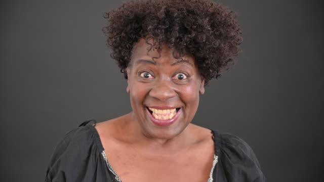 stockvideo's en b-roll-footage met portret van vrolijke midden jaren '60 zwarte vrouw met krullend haar - lage ronde hals