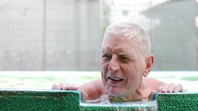 porträt des fröhlichen seniors im schwimmbad - spa stock-videos und b-roll-filmmaterial