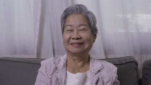 vídeos de stock, filmes e b-roll de retrato de uma idosa alegre relaxando em casa, sorrindo senhora idosa olhando para a câmera postando em casa feliz e graciosamente em sua casa. - vista frontal