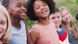 Portrait Of Children Standing On Climbing Frame With Friends In Park