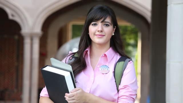stockvideo's en b-roll-footage met portrait of college student wearing vote button. - politieke bijeenkomst