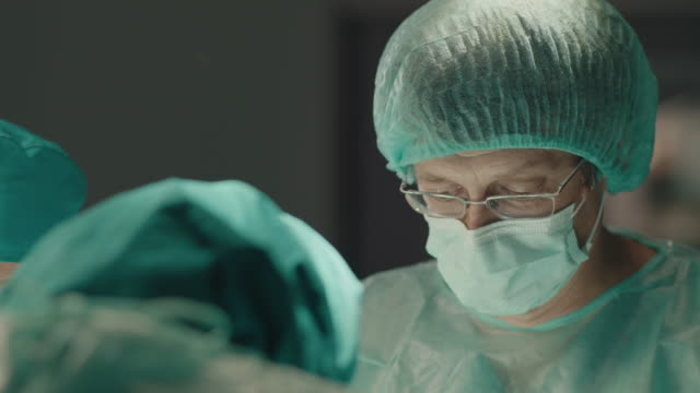 portrait of concentrated middle age surgeon performing surgical operation - surgeon stock videos & royalty-free footage