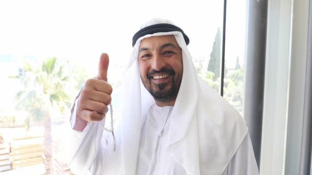 portrait of confident arab businessman showing thumbs up in office - toothy smile stock videos and b-roll footage