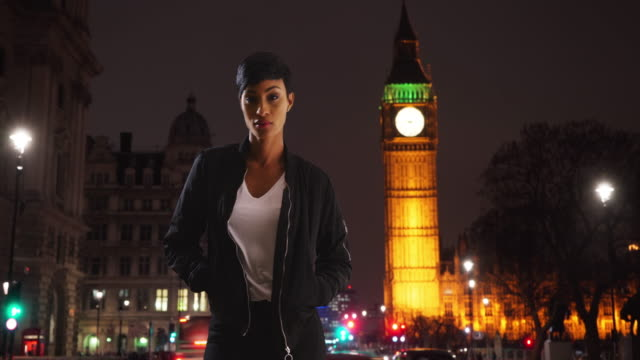 portrait of confident black female on london street, with view of the big ben - big ben点の映像素材/bロール