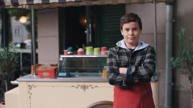 vídeos y material grabado en eventos de stock de portrait of confident boy standing with arms crossed against ice cream stand - apron