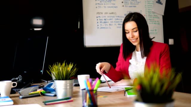 vidéos et rushes de portrait de femme d'affaires confiant écrivant le document s'asseyant au lieu de travail dans le bureau - editorial