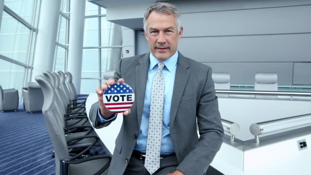 vídeos de stock e filmes b-roll de ms ds portrait of confident businessman in corporate office holding vote pin / virginia beach, virginia, united states - cabelo grisalho
