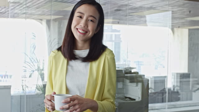 portrait of confident chinese businesswoman with coffee in office - three quarter length stock videos & royalty-free footage