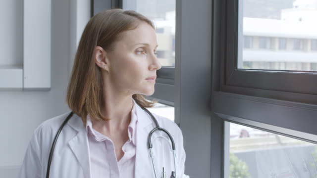 portrait of confident doctor by window in hospital - dottoressa video stock e b–roll