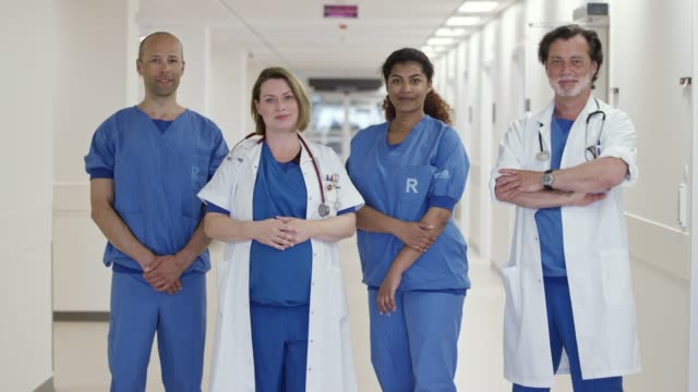 portrait of confident doctors in corridor at clinic - scrubs stock videos & royalty-free footage