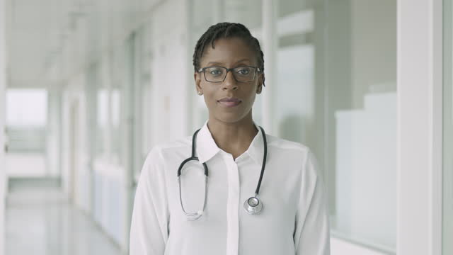 portrait of confident female black doctor standing in hospital corridor looking at camera with stethoscope - female doctor stock videos & royalty-free footage