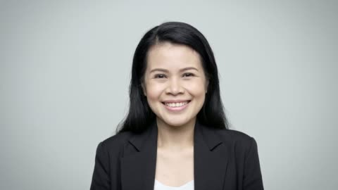 portrait of confident female executive smiling - white background stock videos & royalty-free footage