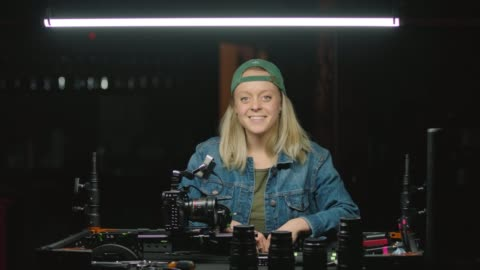 slo mo. portrait of confident female filmmaker at work station attaching new camera lens and looking up to smile at camera - film camera stock videos & royalty-free footage