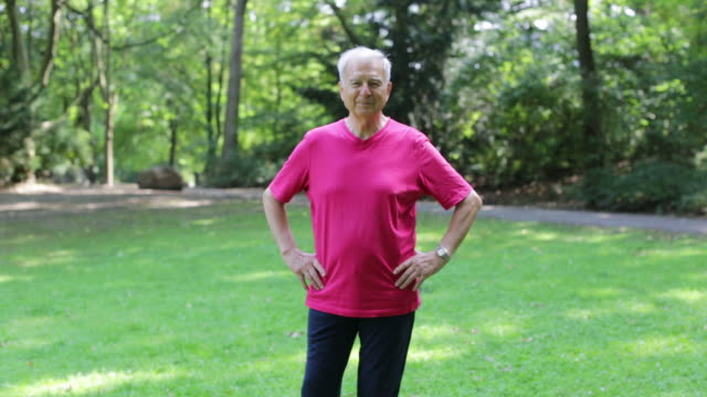 portrait of confident fit senior man smiling in park - hands in pockets stock videos & royalty-free footage