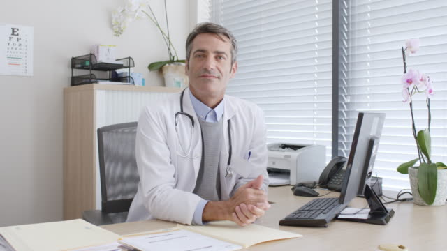 Portrait of confident male doctor sitting at desk