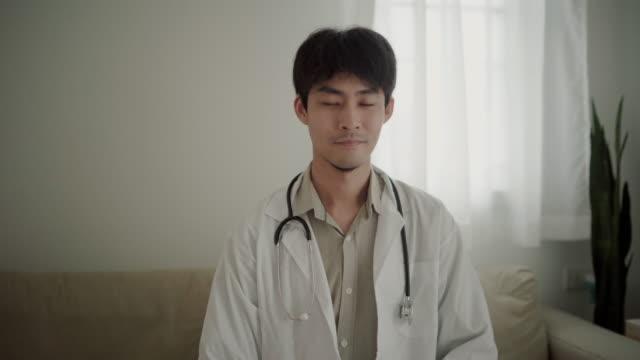 porträt von selbstbewussten männlichen arzt tragen weiße uniform blick auf die kamera - rettungsdienst mitarbeiter stock-videos und b-roll-filmmaterial