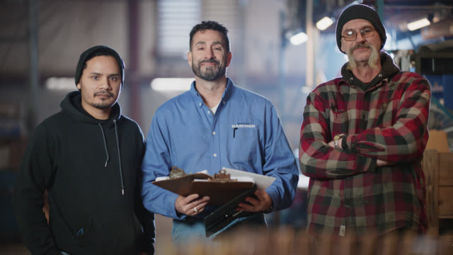 slo mo portrait of confident male industry workers standing in warehouse - three people stock-videos und b-roll-filmmaterial