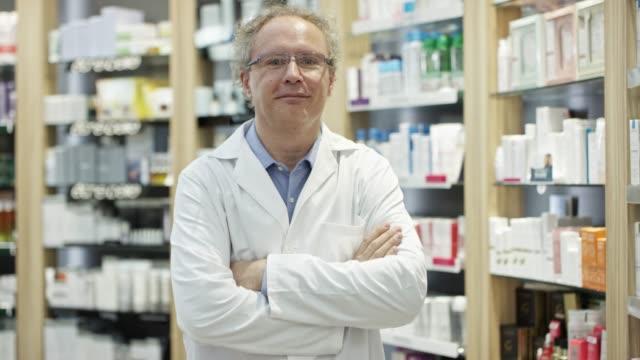 vidéos et rushes de portrait de chimiste mature confiant à la pharmacie - groupe d'objets