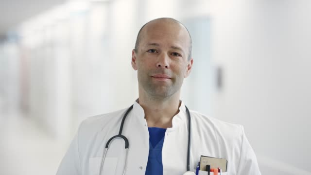 portrait of confident mature doctor at hospital - lab coat stock videos & royalty-free footage