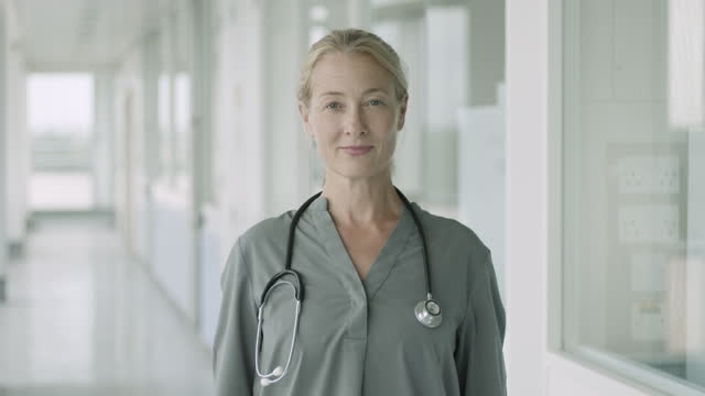 portrait of confident mature female doctor standing in hospital corridor looking at camera with stethoscope - blouse stock videos & royalty-free footage