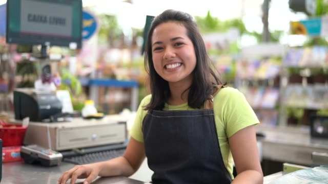 portrait of confident owner leaning on checkout counter at flower shop - shop assistant stock videos & royalty-free footage