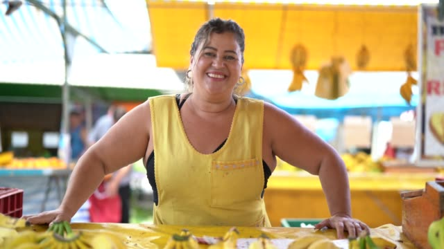 portrait of confident owner - selling bananas at farmers market - bancarella video stock e b–roll