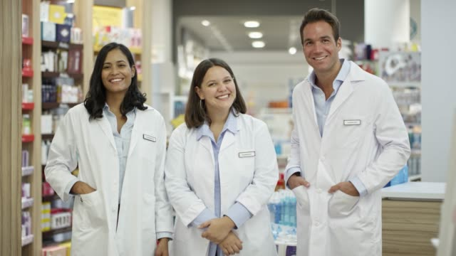 portrait of confident pharmacists in drug store - small group of people stock videos & royalty-free footage