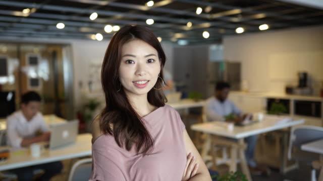 portrait of confident taiwanese woman in office space - piccolo ufficio video stock e b–roll
