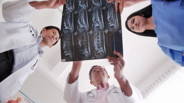 portrait of confident team of doctors, nurses and assistants.medical team checking xray results.professional medical personnel working.medical concept.medical consultation - examining stock videos & royalty-free footage