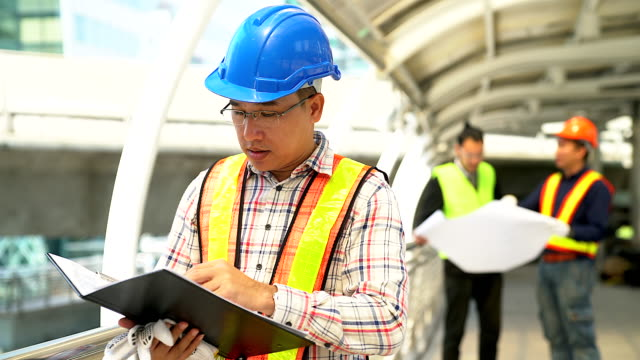 portrait of confident young engineer wearing protective hardhat and holding blueprint. - work helmet stock videos & royalty-free footage
