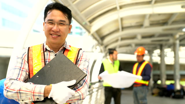 Portrait of confident young engineer wearing protective hardhat and holding blueprint.