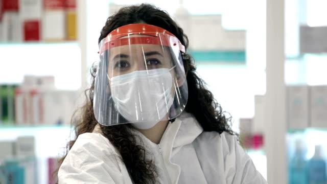 vídeos de stock e filmes b-roll de portrait of confident young female pharmacist in medical mask - máscara cirúrgica