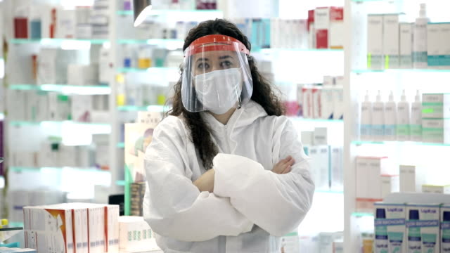 portrait of confident young female pharmacist in medical mask - pharmacy stock videos & royalty-free footage