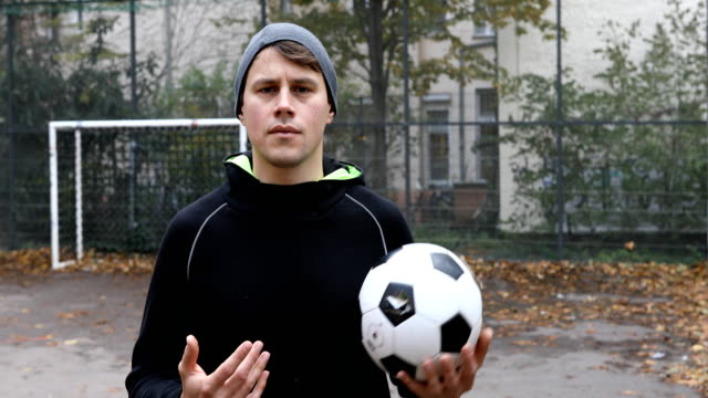 Portrait of confident young man juggling football