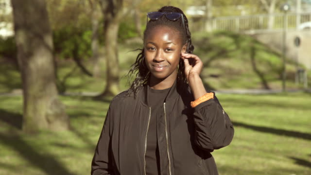 portrait of confident young woman standing at park during sunny day - earring stock videos & royalty-free footage