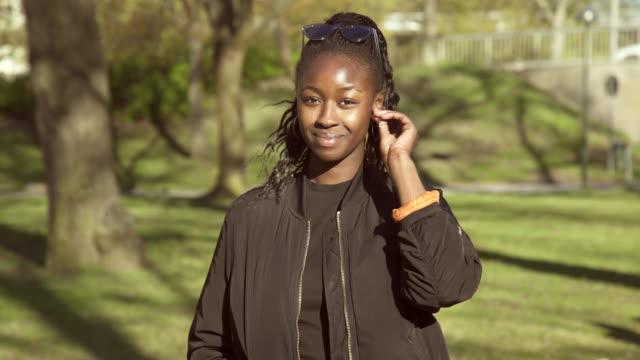 portrait of confident young woman standing at park during sunny day - örhänge bildbanksvideor och videomaterial från bakom kulisserna