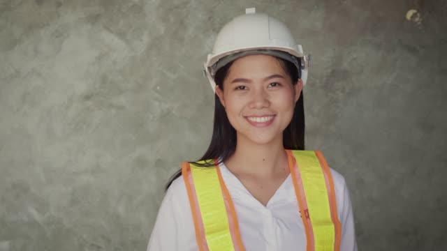 Portrait of construction engineer female with helmet and work vests looking at camera on grey backgrounds