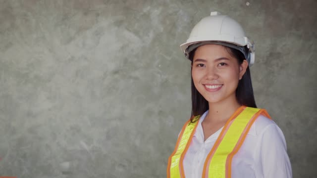 portrait of construction engineer female with helmet and work vests looking at camera on grey backgrounds - building contractor stock videos & royalty-free footage