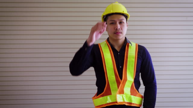 Portrait of construction engineer with yellow helmet and work vests looking at camera