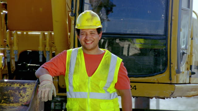ms, portrait of construction worker standing by heavy equipment, san antonio, texas, usa - construction worker stock videos & royalty-free footage