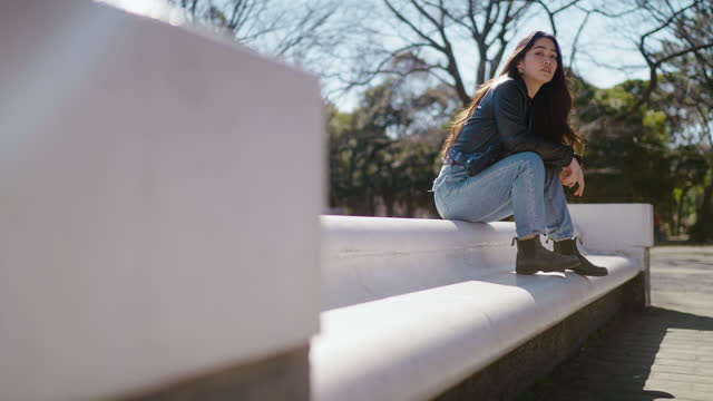 vídeos de stock e filmes b-roll de portrait of cool young and beautiful woman sitting in park and looking at camera - jaqueta jeans