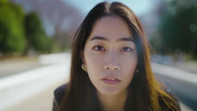 公園に座ってカメラを見ているクールな若くて美しい女性の肖像画 - 真剣点の映像素材/bロール
