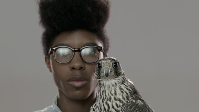 Portrait of cool young man, falconer with his falcon
