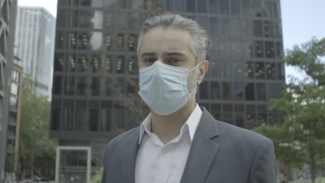 portrait of corporate business man wearing face mask in the city of london during covid-19 pandemic - middle eastern ethnicity stock videos & royalty-free footage
