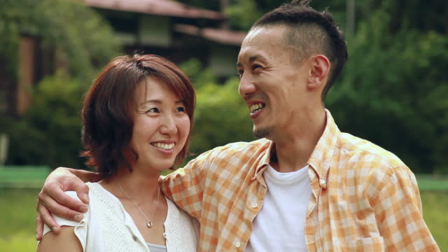 CU Portrait of couple embracing and smiling / Tokyo, Japan